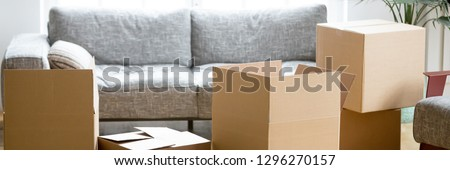 Horizontal photo heap of cardboard boxes with personal belongings in living room at moving relocation day no people, delivery service concept, banner for website header design with copy space for text