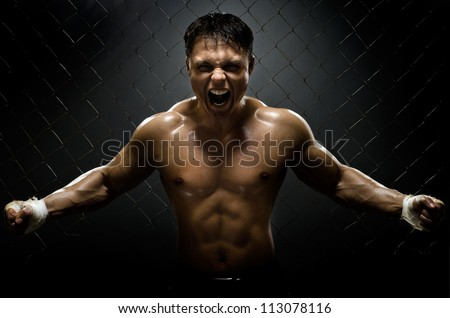 horizontal photo  muscular young  guy street-fighter,  aggression frightening  yell , hard light