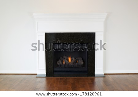 Horizontal photo of a natural gas fireplace with a white mantle and cherry wood floors