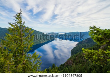 Horizontal photo of a View of Lake Crescent in Olympic National Park from Storm King with blue skies and clouds reflecting in the blue water. Mountains and hills in the background with evergreen trees