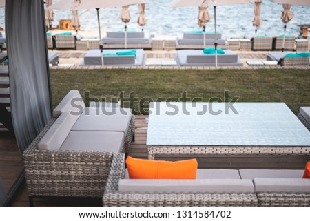 Horizontal photo of empty terrace of seaside cafe with table and couches and sea on the background