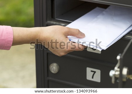 Horizontal photo of female hand pulling out letters from postal mailbox with green grass and sidewalk in background