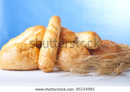 horizontal photo of fresh baked bread with wheat over light blue background