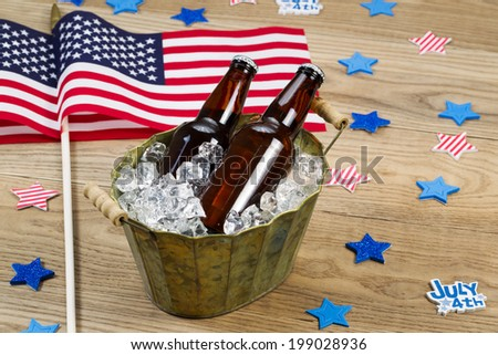 Horizontal photo of glass bottled beer in old metal bucket filled with ice and American flags in background for celebration of Independence Day