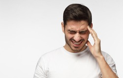 Horizontal photo of good-looking Caucasian man pictured isolated on gray background in right side of picture showing how much his head hurts, experiencing pain, looking miserable and exhausted