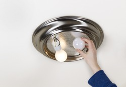 Horizontal photo of hand taking out light bulb- incandescent type- with one bulb burnt out and one working