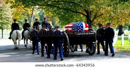 Horizontal photo of Honor Guard at Arlington National Cemetery marching with caisson carrying casket to grave site