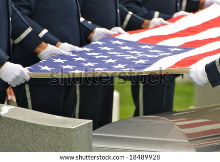 Horizontal photo of honor guard holding flag over casket at Arlington National Cemetery