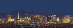 Horizontal photo of Las Vegas with mountain backdrop at night.