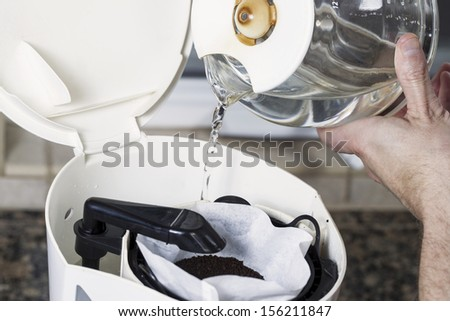 Horizontal photo of male hand pouring water, from coffee pot, into coffee maker with fresh coffee grounds in white bleached coffee filter with stone kitchen counter top