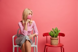Horizontal photo of middle aged blonde woman wears disposable face mask looks thoughtfully aside on cactus pot dressed in neat clothing poses against vivid crimson background at comfortable chair