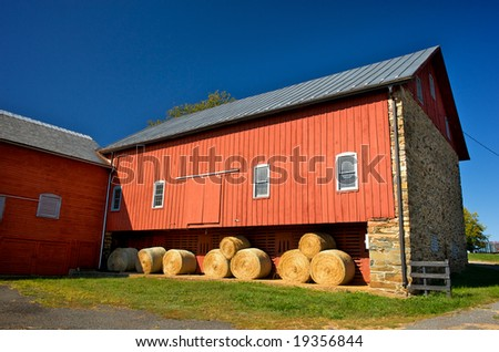 Horizontal photo of red barn with stone wall and bales of hay