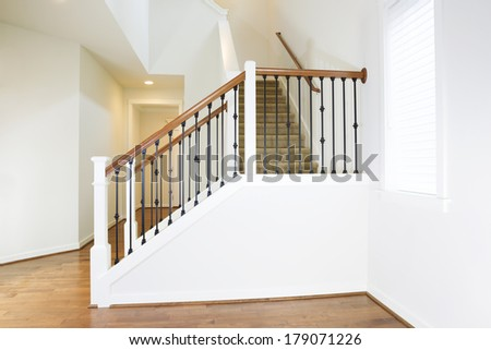 Horizontal photo of residential hard wooden floors and custom staircase made of iron and wood railing with carpet on steps
