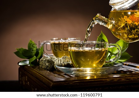 horizontal photo, of the glass teapot flow green tea in cup on brown background,  tea ceremony