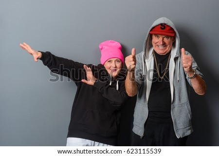 Horizontal photo of two old people dancing in front of a gray wall. Grandad shows thumbs up, granny raised her hands aside. Funny grandparents in modern clothes have a good time.