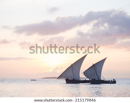 Horizontal photo of two traditional Tanzanian dhow boats on open sea on Indian Ocean close to Stone Town on Zanzibar island, Tanzania in East Africa, at sunset.