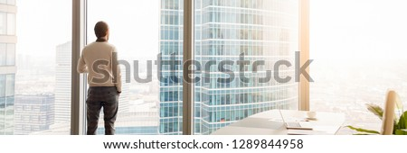 Horizontal photo rear back successful businessman look through window at big city, rest has break, think about future business vision concept, banner for website header design with copy space for text #1289844958