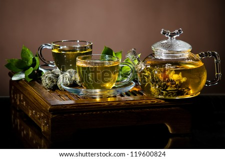 horizontal  photo  still life of the glass teapot with green tea and two cup on  wooden trivet