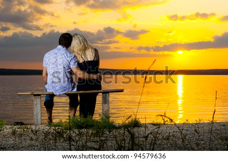 horizontal photo the  happy  couple, outdoor on beauty sunset or sunrise, on beach