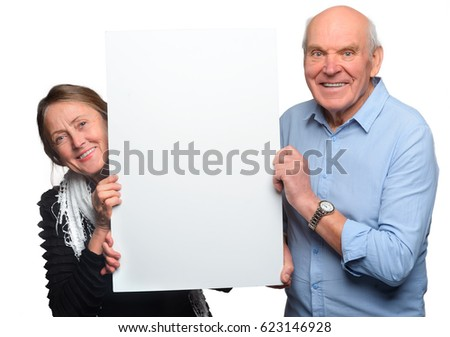 Horizontal pic of grandparents pose with empty placard on white background. Smiling pensioners hold a big white canvas for your text or picture.