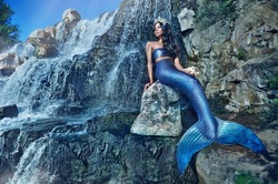 Horizontal picture of a mermaid sitting on the rock of the waterfall