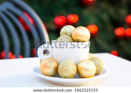 Photo of Horizontal picture of coffee cup with golden Christmas balls inside and around. Coffee pair on white table angle, grey chair, new year tree with red toys in background. Winter cafe. Post card picture