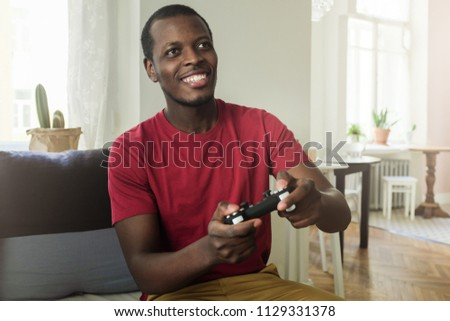 Horizontal picture of young handsome African man spending free time in his room on couch playing video games with help of game console, smiling, feeling satisfied with gaming process and success