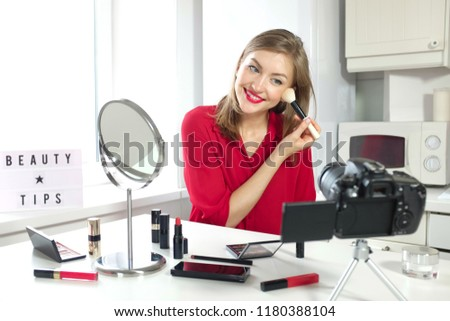 Horizontal picture of young positive European female sitting at table with mirror, beauty products lying around, looking at camera on table, smiling while showing how to apply powder with brush
