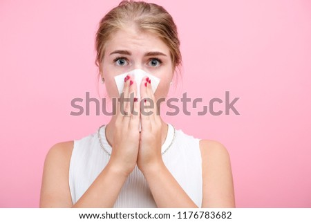 Horizontal portrait a young ill girl with a handkerchief and runny nose, looking into the camera, white skinned female model at pink wall isolated. - Shutterstock ID 1176783682