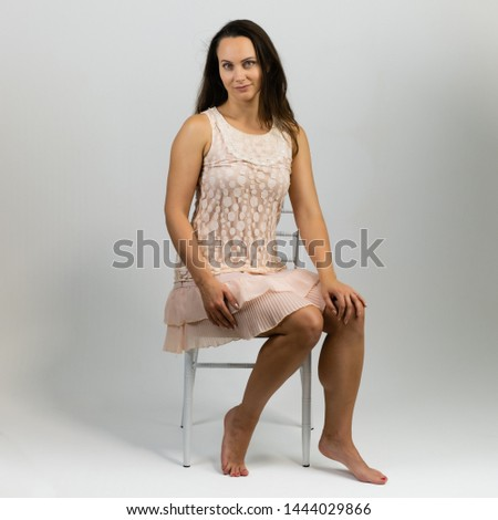9f1d4e59ac919 Horizontal portrait full length sitting on a white chair on a white  background beautiful pretty woman