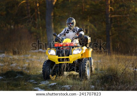 Horizontal portrait of a man in helmet and safety goggles looking into the camera while sitting on all-terrain vehicle against snowy late autumn landscape. Stock photo ©