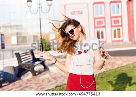 Horizontal portrait of a standing widely smiling and dancing young girl holding a smartphone and listening to music. Girl wears a white t-shirt, red skirt and dark sunglasses. #454775413