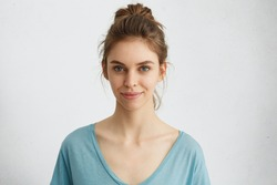 Horizontal portrait of attractive blue-eyed female dressed casually having delightful look while smiling. Beautiful woman with hair bun having cheerful expression while posing at studio over white