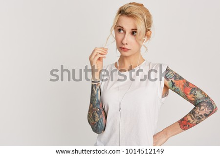 Stock Photo Horizontal portrait of blond, european girl with pierced nose, blue eyes, tattoo on arms, dressed in casual white t-shirt, listen music via headphones  and looking aside. Copyspace. Isolated