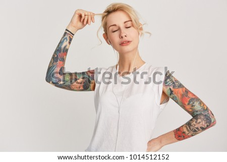 Stock Photo Horizontal portrait of blond, european girl with pierced nose, closed eyes, tattoo on arms, dressed in casual white t-shirt, listen and enjoy music with earphones. Isolated on white wall