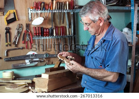 horizontal portrait of carpenter examining handmade pieces of wood workshop / work cabinetmaker looking handcrafted wooden pieces in garage at home