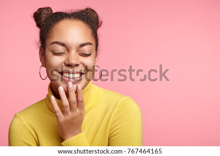Horizontal portrait of cheerful African female being pleased with something, closes eyes, demonstrates charming smile with perfect white teeth, glad to recieve good news, isolated over pink wall #767464165