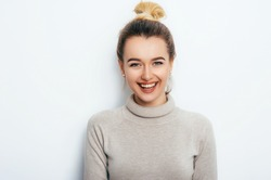 Horizontal portrait of cheerful woman with appealing smile, having hair bun wearing in sweater isolated over white background.  Beautiful female showing her pleasant emotions. People Beauty Fashion