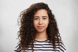 Horizontal portrait of curly mixed race beautiful woman with dark eyes and full lips dressed casually, being delightful to be at home alone. Attractive young female model poses in white studio