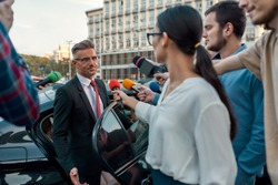 Horizontal portrait of disgruntled man getting out of the car to answer questions of journalists. They attack him holding microphones in order to get exclusive interview. Selective focus on man