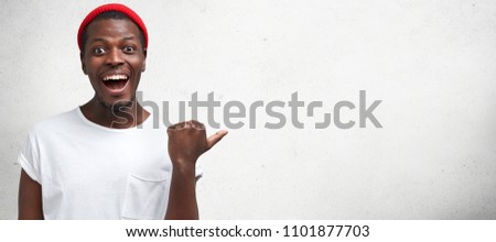 Horizontal portrait of good looking cheerful African American male points left with thumb and positive smile, suggests great copy space for your advertisement, dressed in fashionable clothes. #1101877703