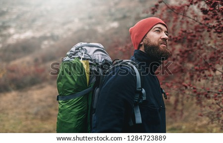 Horizontal portrait of hiker young male hiking in mountains with travel backpack. Traveler man with beard trekking and mountaineering. Travel, people, healthy lifestyle concept