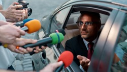 Horizontal portrait of man looking out the car window and answering questions of journalists. They attack him holding microphones in order to get exclusive interview. Selective focus on man