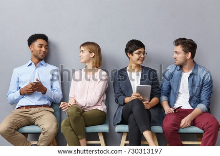 Horizontal portrait of people sit in queue, have pleasant conversation with each other, share ideas and life experience, isolated over grey concrete wall. Diverse group in row, speak and hold gadgets #730313197