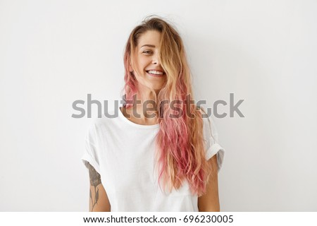 Horizontal portrait of pleasant-looking Caucasian female with long hair, pink on tips, having tattooes on arms, wearing white casual T-shirt, covering her face with hair, looking happily in camera #696230005