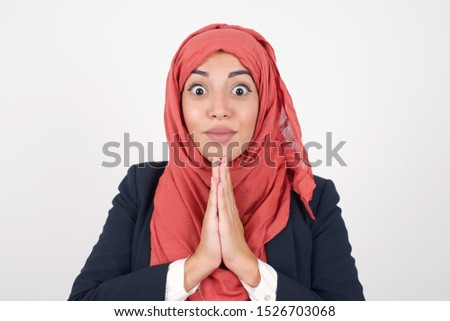 Horizontal portrait of pretty muslim woman keeps palms together, has pleased expression. Glad attractive female makes request,  Hopeful young adult.