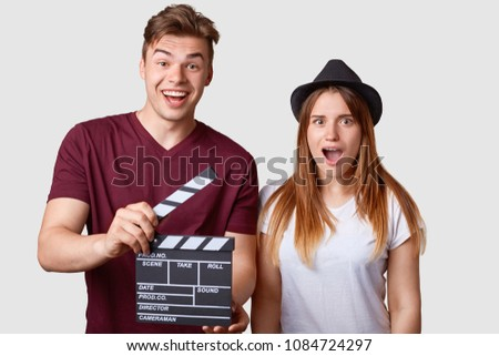 Horizontal portrait of shocked young successful female actress and her producer holds clapperboard, has cheerful expression, creat new production of film, stand close to each other, isolated on white #1084724297