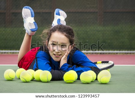 Horizontal portrait of smiling teenage girl tennis player laying on the outdoor court behind a row of tennis balls with head resting in her hand and feet in air