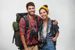 Horizontal portrait of smiling young female and male hikers with huge backpacks, embracing each other, having happy expressions after long journey and successful exploration of unknown places