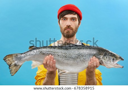 Horizontal portrait of successful angler with beard holding huge fish which he catched. Young fisherman dressed casually standing with huge trout. Man with fresh catch. Fishing and recreation